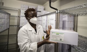 A technician shows a carton of AstraZeneca COVID-19 vaccine at the central vaccine depot in Kitengela town on the outskirts of Nairobi.