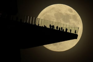 New York, US: A full moon rises behind people standing on Edge, an outdoor observation deck in Manhattan