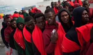 Migrants rescued at sea wait to be transferred at the harbour of Algeciras.