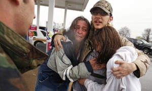 Dacia Winters, left, embraces Ryan Ficca, center, and Stormy Winters after they were evacuated in a Louisiana national guard high water vehicle from rising floodwaters in Bossier Parish, Louisiana.