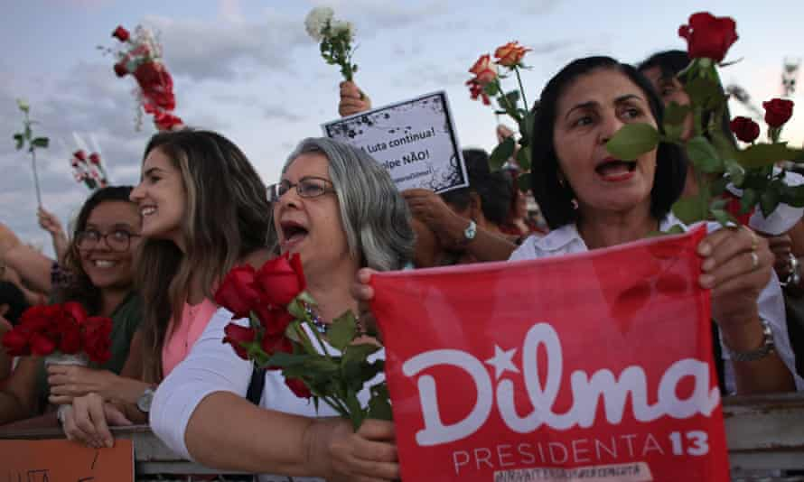Women carrying flowers take part in a demonstration against the impeachment process of Dilma Rousseff