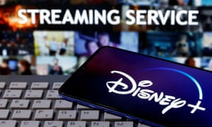 """A smartphone with displayed """"Disney"""" logo is seen on the keyboard in front of displayed """"Streaming service"""""""