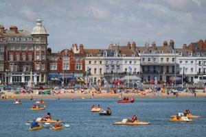 Weymouth, UK. People take to the sea in pedalos off the Dorset coast