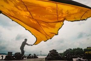 Kolkata, India: A man dries a traditional triangular flag for the Islamic festival Muharram near the Ganges River