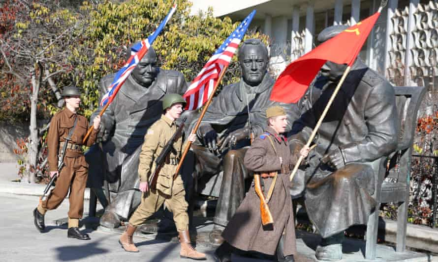 Participants dressed as soldiers with the flags of the United Kingdom, the United States and the Soviet Union walk past a monument to Winston Churchill, Franklin Roosevelt, and Joseph Stalin in Yalta on 4 February.