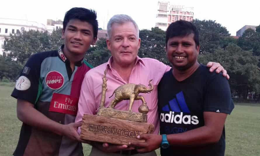 Tim Grandage poses with the club's captain and coach with a special trophy.