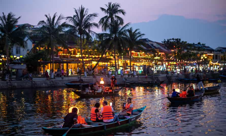 people in boats on water near a brightly lit building and palm trees