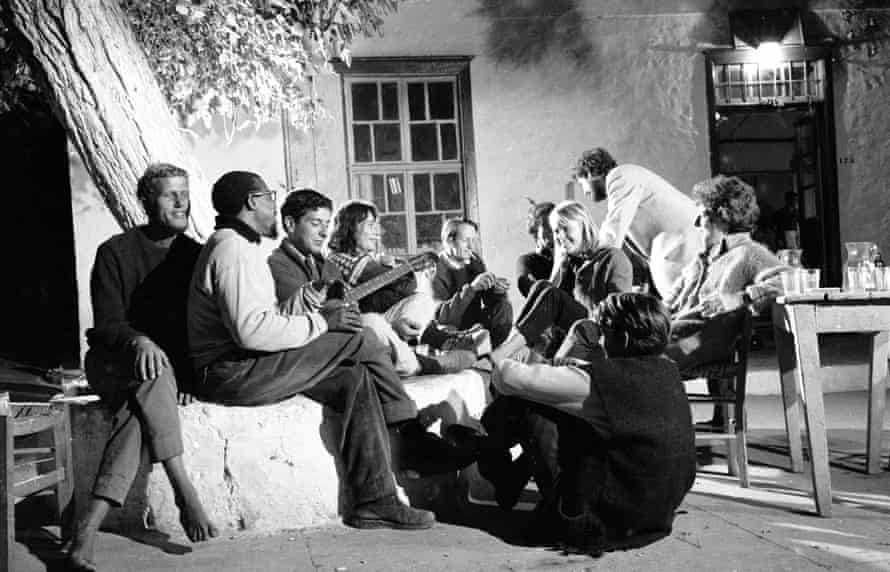Leonard Cohen (holding the guitar) with Marianne (looking at him) and friends in Hydra, Greece, October 1960