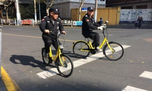 Security guards in Shanghai ride Ofo share bikes.