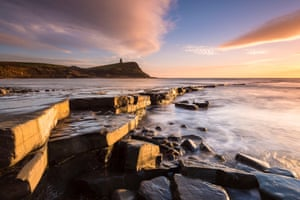 Warm sunlight bathes the landscape during sunset at Kimmeridge Bay on the Jurassic Coast of Dorset