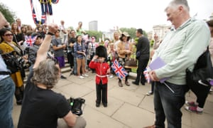 A young boy dressed in a guardsman costume poses for the cameras before the royal procession makes its way down the Mall from Buckingham Palace to Horse Guards Parade