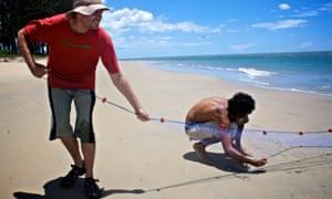 Tourist and fisherman on idyllic beach