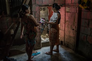 Rhoda hands over an Avon purchase to her neighbour, as her business has begun to slowly expand, on the first floor of her house, she was forced to abandon due to recurring flooding.