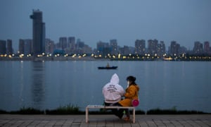 A couple sit by the river in Wuhan. Life in Wuhan is gradually back to normal as the coronavirus outbreak wanes.