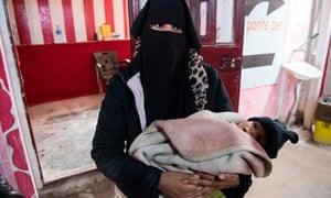 A Syrian woman holding a child waits at a makeshift clinic at al-Hawl