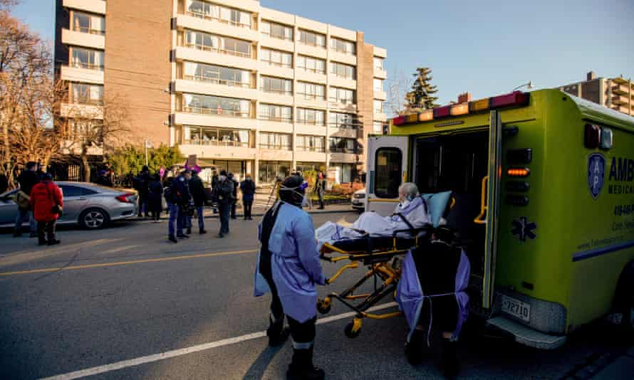 A woman is placed in an ambulance outside the Sienna St George long-term care home in Toronto on Thursday.
