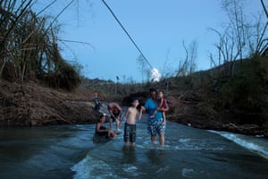 Puerto Ricans in San Lorenzo in the river after Hurricane Maria destroyed the town's bridge, October 2017.