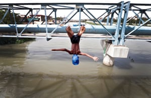 A boy jumps from a water pipe into a canal in New Delhi, India