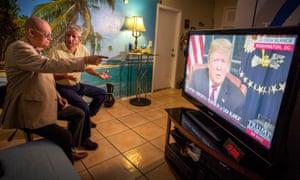 Miguel Saavedra and Oswaldo Hernandez  watch Donald Trump on TV