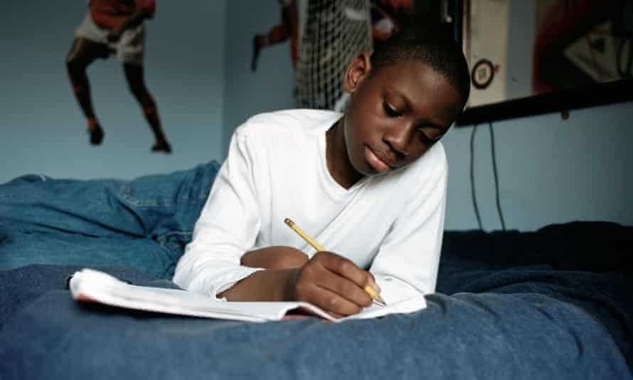 Boy doing homework on bed