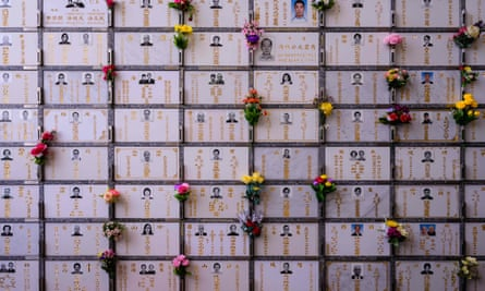 Flowers are placed next to photos of deceased loved ones at a Hong Kong columbarium during the Qingming festival.