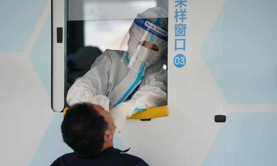 Medical worker collects a swab from a man for nucleic acid testing in Beijing