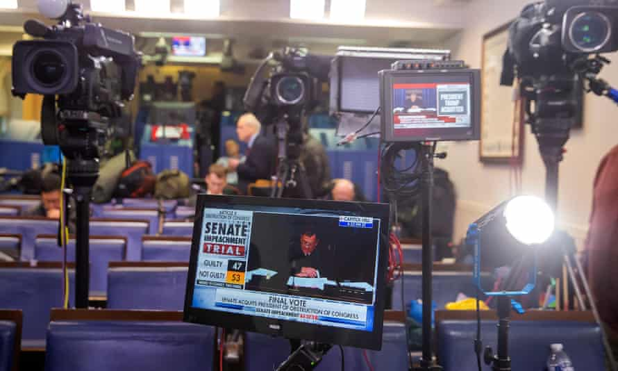 Members of the media watch TV monitors as the Senate votes to acquit Trump