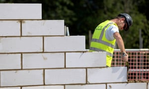 Construction worker cementing bricks