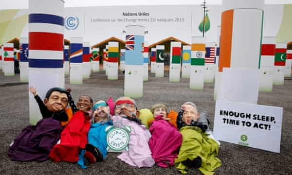 Demonstrators wear heads of world leaders during the Paris climate summit.