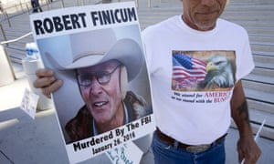 Randy Peck of Las Vegas, a supporter of Nevada rancher Cliven Bundy, holds a sign of LaVoy Finicum in downtown Las Vegas.