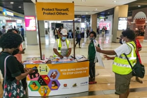 Shoppers learn about COVID-19 in Port Moresby.