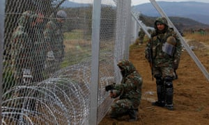 Macedonian soldiers erect a barbed wire fence on the Macedonia-Greece border
