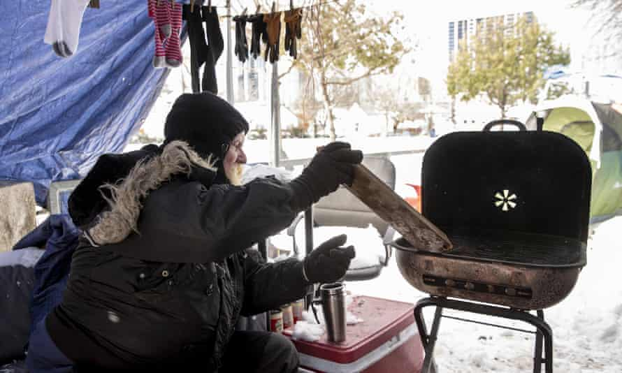 Tim tends a fire he used for heat and cooking at a homeless camp in Austin, Texas, during an extreme cold snap in February.