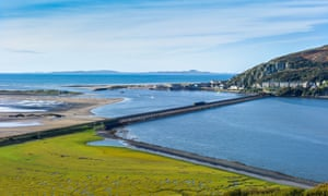 A panoramic view with a Cambrian coast train crossing Barmouth Bridge.