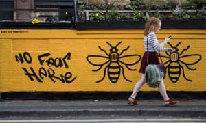 A woman passes graffiti created after the terror attack