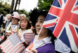 A Japanese woman waves a union flag as she waits for the arrival of world leaders at Ise grand shrine