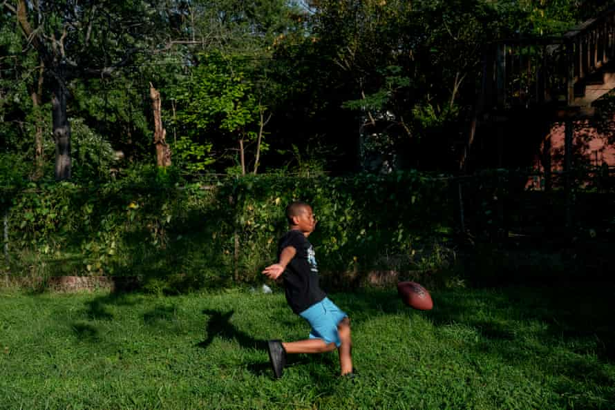 Damontez Sharp, 9, plays football in an empty lot between his grandmother's and neighbor's house in St. Louis on Thursday, Sept. 12, 2019. His grandmother, Chante Bass, prefers the children play between the houses rather than in the front yard where they're more exposed. The family lives in north St. Louis, which has long been plagued by gun violence. At least 13 children have died of gunshot wounds in St. Louis city this year, and six children in St. Louis Country have been killed by gunfire.