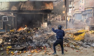 Clashes Over Citizenship Amendment Law Kill Two In India's National Capital<br>DELHI, INDIA - FEBRUARY 24: An Indian protester throws bricks on a building set ablaze during clashes between two groups over the Citizenship Amendment Act on February 24, 2020 in Delhi, India. An Indian policemen and a civilian were killed as clashes erupted between two groups over the Citizenship Amendment Act, a controversial law passed by the Indian government that has led to protests over fears that it will be used to strip the country's Muslim population of their citizenship. Demonstrations were held in Shaheen Bagh, a Muslim majority locality where hundreds of women are holding a sit-in protest over the past two months, against the visit of US President Donald Trump to India.  (Photo by Yawar Nazir/ Getty Images)
