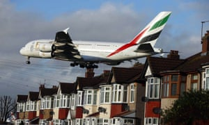 An Emirates Airbus A380 landing over houses near Heathrow airport.