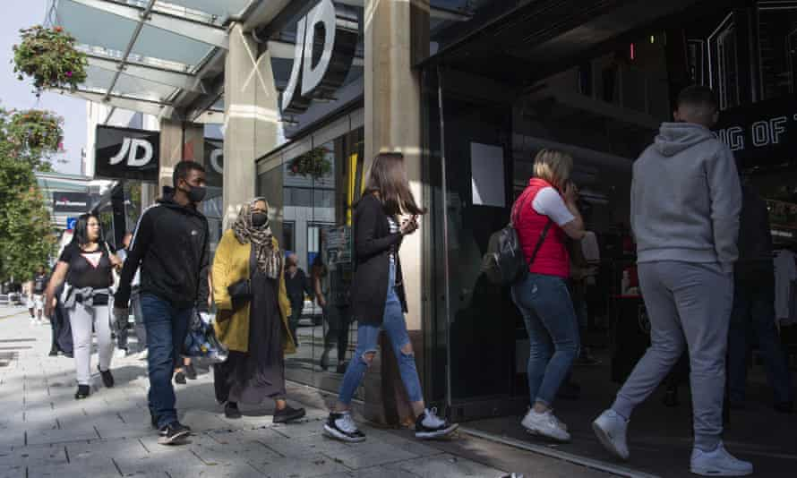 Shoppers queue outside JD sports in Cardiff in June.
