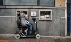 A woman in a powered wheelchair scooter using a cash machine