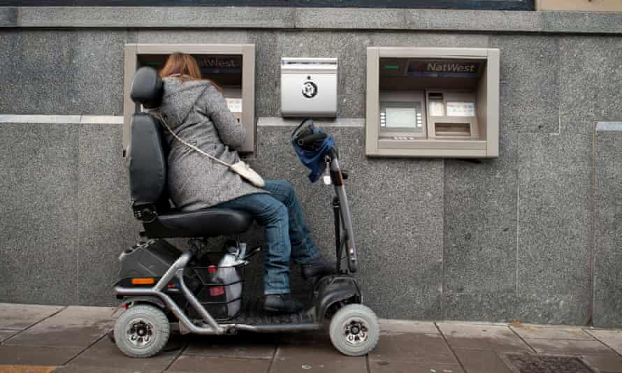A woman in a mobility scooter using an ATM