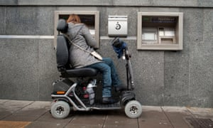 A woman in a powered wheelchair scooter using an ATM cash machine