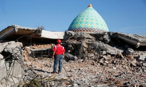 A rescue worker looks at the remains of a collapsed mosque in Lombok after an earthquake