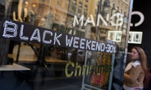 A shopper enters a Mango retail store advertising 'Black Friday' discounts in Madrid, Spain.