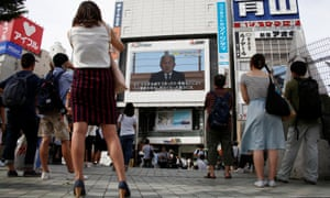 People watch Akihito's address in Tokyo.