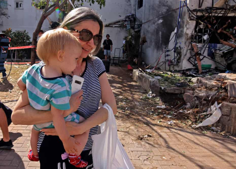 A woman carries her child outside a building which received a direct hit by rockets from the Gaza Strip, in the southern Israeli city of Ashdod on Monday.