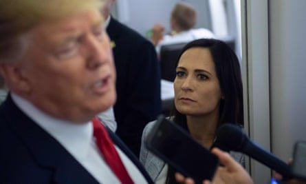 Stephanie Grisham listens as Donald Trump speaks to reporters aboard Air Force One on 7 August 2019.