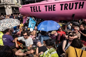 Protesters sit by the pink boat painted with the words: 'Tell the truth'