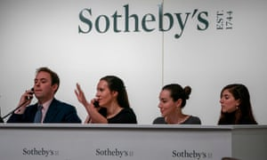 Sotheby's employees take phone bids on an artwork in an auction in New York.